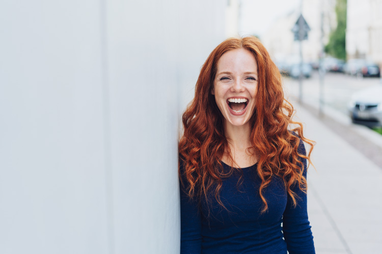 Red-haired woman with dental implants smiles while standing against a white wall