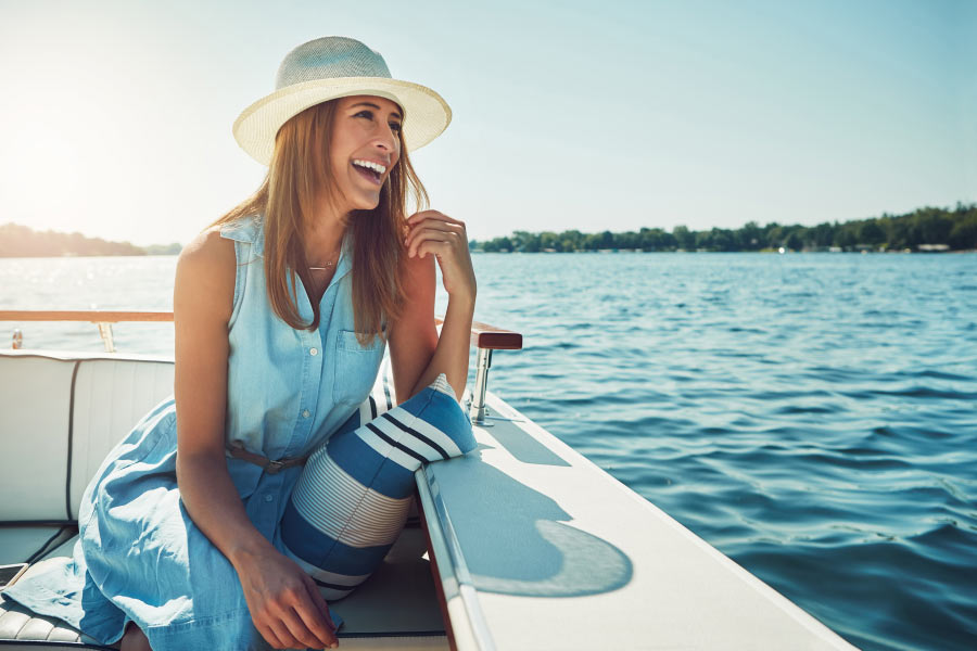 Brunette woman with a beautiful smile after cosmetic dentistry relaxes on a boat in the water